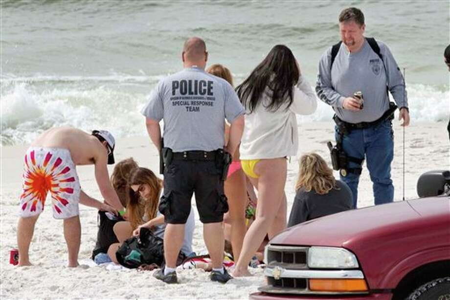 Officers with Florida's Division of Alcoholic Beverages and Tobacco check the IDs of spring breakers on the beach near Destin, Florida. Since Saturday, officials with the Walton County Sheriff's Office have issued more than 200 citations for underage drinking and have busted two house parties with more than 100 spring breakers. Photo: Devon Ravine, AP / Northwest Florida Daily News