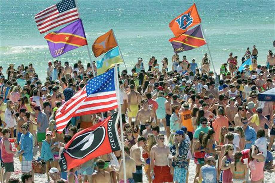 Thousands of spring breakers from around the southeast converge on the beach near the Whale's Tail Restaurant in South Walton County, Florida on Wednesday, March 13, 2013. As college spring breakers make their annual pilgrimage to beaches along the northwest Florida Gulf Coast, local law enforcement personnel are making regular sweeps looking for underage drinkers and managing unurly behavior. Photo: DEVON RAVINE, AP / NORTHWEST FLORIDA DAILY NEWS