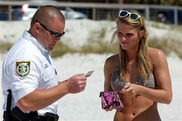 Walton County Deputy Sheriff Brad Barefield, left, checks the IDs of Jenna Harris and other spring breakers from Mississippi on the beach in South Walton County, Florida on Wednesday, March 13, 2013. Photo: DEVON RAVINE, AP / NORTHWEST FLORIDA DAILY NEWS