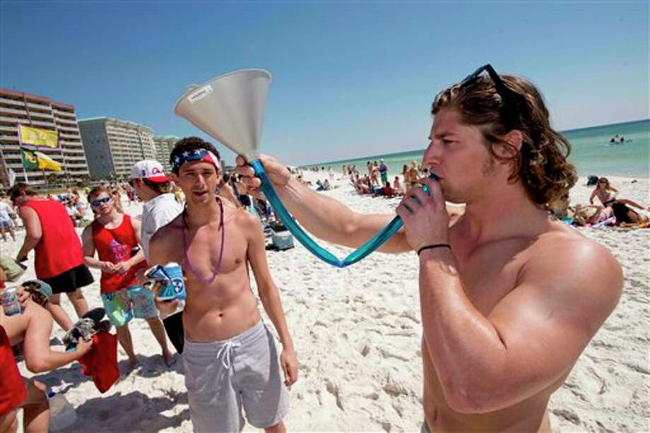 Drew Moyes, right, prepares to use a funnel to consume a beer as fellow spring breaker Max Molteni watches on the beach in South Walton County, Florida. Photo: DEVON RAVINE, AP / NORTHWEST FLORIDA DAILY NEWS