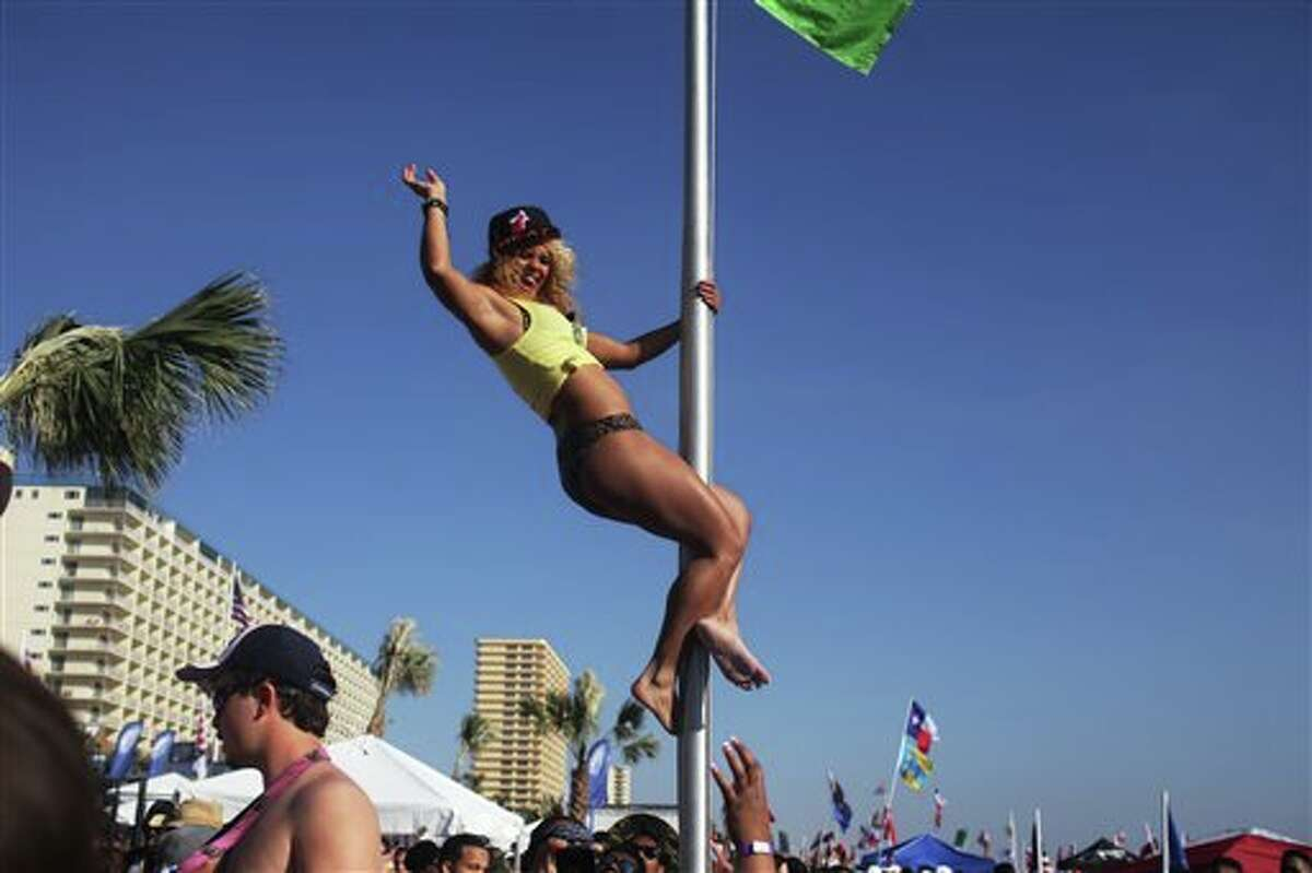 Shayla Brown, a student at Tallahassee Community College, dances from a flag pole on the beach in Panama City Beach, Fla., on Thursday, March 14, 2013.