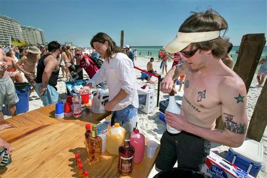 David Lightsey, right, and Chad Henson serve up drinks at the Two Stick Restaurant's free bar, which was set up on the beach in South Walton County, Florida on Wednesday, March 13, 2013. Henson set up the free bar in the center of a crowd of spring breakers from the University of Mississippi to promote the restaurant he owns in Oxford, Mississippi as well as another he plans to open in Destin, Florida. Photo: Devon Ravine, AP / NORTHWEST FLORIDA DAILY NEWS
