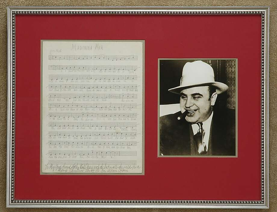 "A photo of Al Capone and sheet music for a song ""Madonna Mia"" written in pencil by Capone while he was at Alcatraz prison. More than 70 years after Capone penned it, somebody recorded the song. Photo: AP"