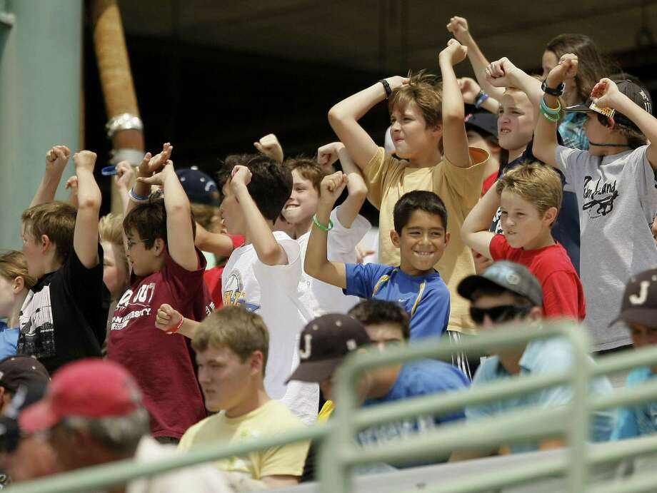 Students cheer during a minor league baseball game between the San Antonio Missions and the Corpus Christi Hooks. A soldier writes about how an act of kindness by a minor league ball player helped his young son while the solider was away. Photo: Darren Abate, For The Express-News