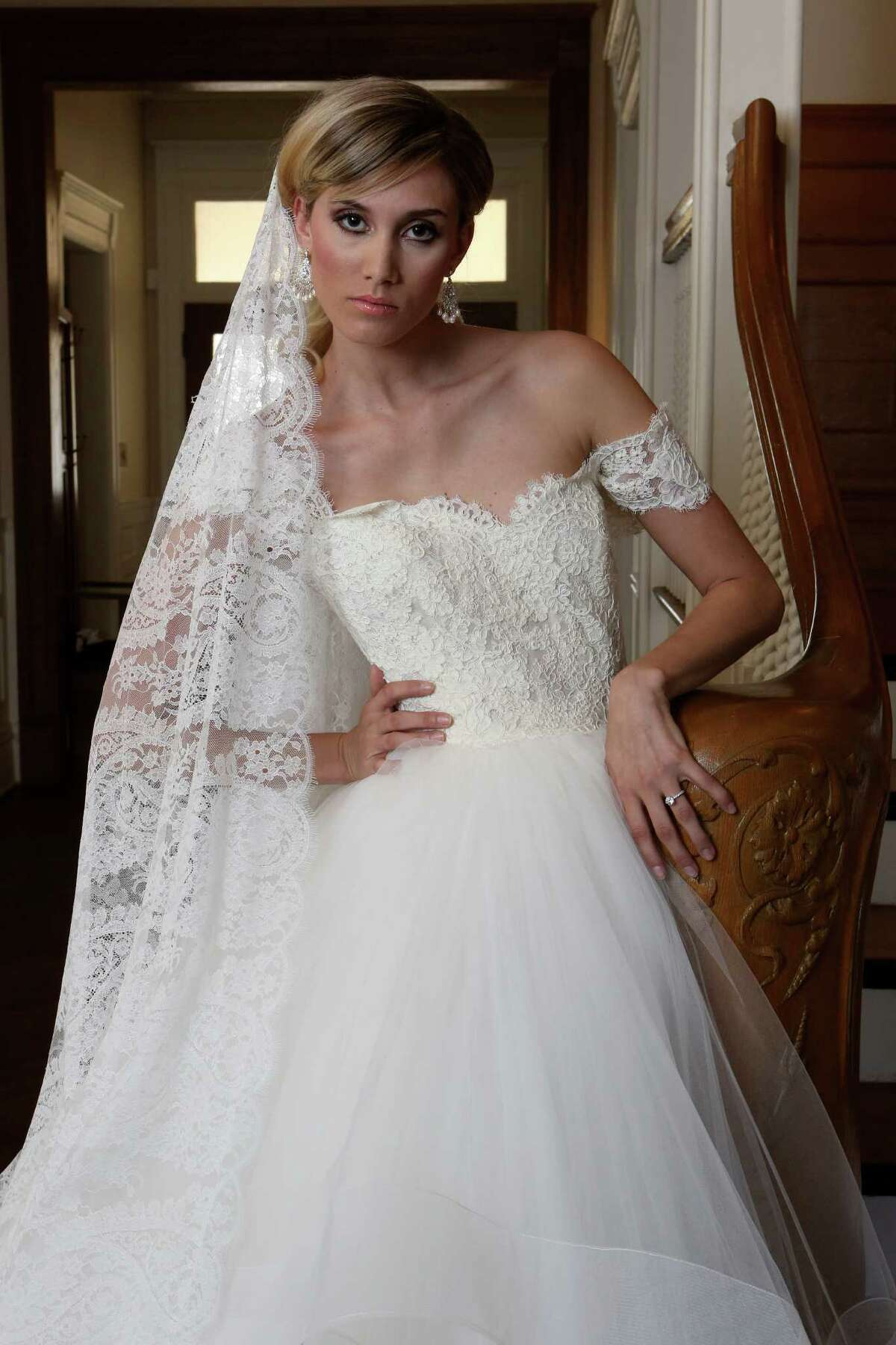 Brooke Vu wears a Jim Hjelm gown with a silk satin-faced organza bodice and trumpet silk skirt of embroidered ivory petals. The gown features a crystal-accented waistline, $6,259. Pearl-adorned mini-chandelier earrins, $165. Gown and earrings from the Bridal Salon of San Antonio, (210) 828-7931. On her head is a rhinestone-studded headband, $375, by Les Accessoires, Bridal Galleria of Texas, (210) 342-5752.