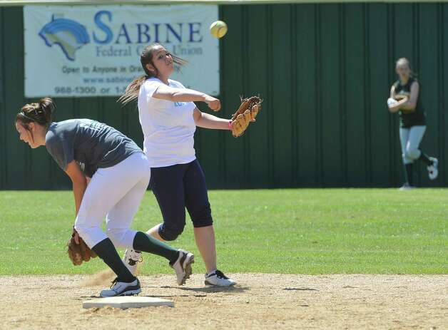 Third baseman Kassie James, right, throws the ball to first base after catching the ball hit ball by her coach Dena Adkins who was batting from home plate. The Little Cypress-Mauriceville softball team is currently  ranked sixth in class 4A. In recent years, they have been one of the best teams in Southeast Texas and are currently leading the district. They were out practicing Thursday afternoon March 14, 2013 getting prepared for their Friday match up with Lumberton High School. Dave Ryan/The Enterprise