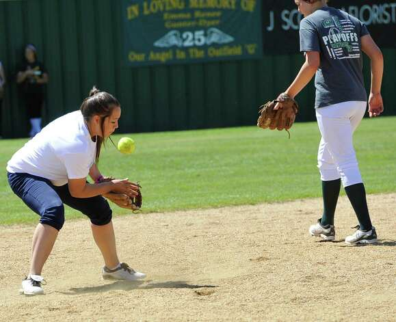 Third baseman Kassie James, left, tries to trap a hit ball by her coach Dena Adkins who was batting from home plate. The Little Cypress-Mauriceville softball team is currently  ranked sixth in class 4A. In recent years, they have been one of the best teams in Southeast Texas and are currently leading the district. They were out practicing Thursday afternoon March 14, 2013 getting prepared for their Friday match up with Lumberton High School. Dave Ryan/The Enterprise Photo: Dave Ryan