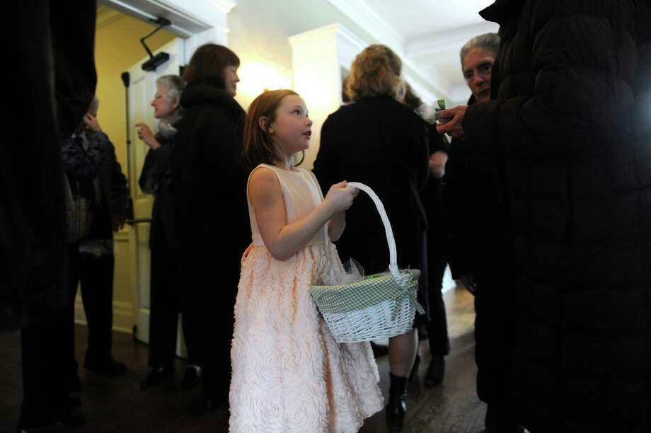 One of Briggs Baugh's grandchildren, Madison Chadwick, 8, gives a guest a bulb tied with green ribbon to remember Baugh during the memorial service at the Stanwich Congregational Church, in Greenwich, Conn., Monday, March 18, 2013.  Baugh, who was 85, died of cancer March 7 at Paradigm Healthcare Center in Norwalk. Not only was Baugh the town's first recycling coordinator, a position created in the Department of Public Works, but he spearheaded a joint volunteer effort to collect cans and paper goods with Greenwich High School in observance of Earth Day. Photo: Helen Neafsey / Greenwich Time