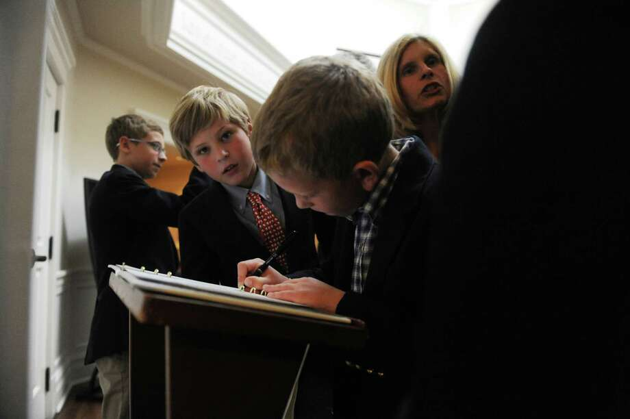 Luke Dehmel, 8, right, writes on a guest book, while his brother Austin, 11, watches during the memorial service for Briggs Baugh at the Stanwich Congregational Church, in Greenwich, Conn., Monday, March 18, 2013. Baugh, 85, died of cancer March 7 at Paradigm Healthcare Center in Norwalk. Not only was Baugh the town's first recycling coordinator, a position created in the Department of Public Works, but he spearheaded a joint volunteer effort to collect cans and paper goods with Greenwich High School in observance of Earth Day. Photo: Helen Neafsey / Greenwich Time