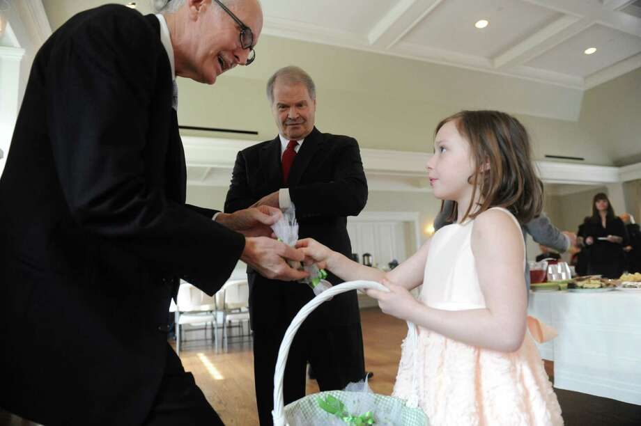 Ron Jaco, left, receives a bulb to remember Briggs Baugh, from Madison Chadwick, 8, while Les Madorsky watches during the memorial service for Baugh at the Stanwich Congregational Church, in Greenwich, Conn., Monday, March 18, 2013. Baugh, 85, died of cancer March 7 at Paradigm Healthcare Center in Norwalk. Not only was Baugh the town's first recycling coordinator, a position created in the Department of Public Works, but he spearheaded a joint volunteer effort to collect cans and paper goods with Greenwich High School in observance of Earth Day. Photo: Helen Neafsey / Greenwich Time