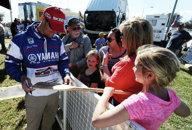 Angler Jared Miller signs an autograph for Madison Murdock, 12, of Mauriceville after weigh in on the second day of the 2013 Bassmasters Elite Series Sabine River Challenge. Photo taken: Randy Edwards/The Enterprise
