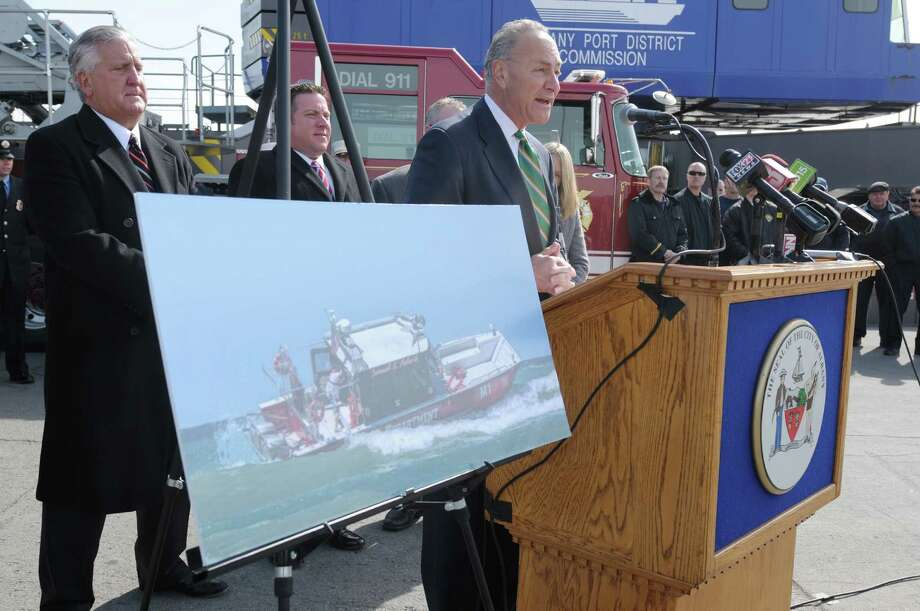 Albany Mayor Jerry Jennings, left, Albany County Executive Dan McCoy, center, look on as Senator Charles Schumer addresses those gathered for a press event at the  Port of Albany on Monday, March 18, 2013 in Albany, NY.  The press conference was held to announce that the Albany Fire Department would be purchasing a rescue boat to be used at the port and the area communities.  The photograph in the foreground is the same type of boat that the department will be getting.  (Paul Buckowski / Times Union) Photo: Paul Buckowski