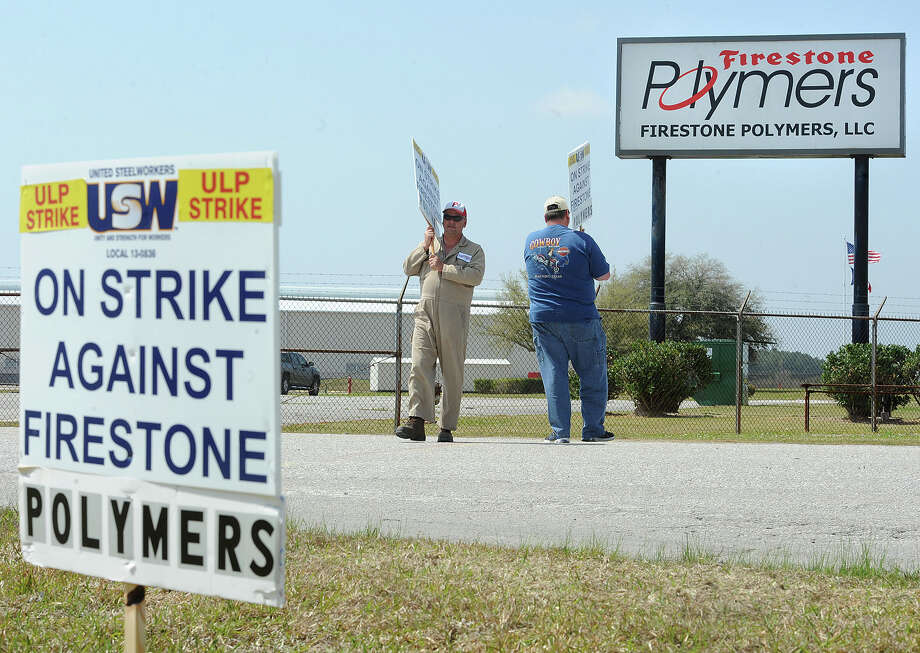 Members of Local No. 13-836 of the United Steelworkers union began striking Monday at Firestone Polymers in Orange after negotiations failed to resolve issues that included a wage increase and health insurance deductibles. The union has 108 members who will work in four-member shifts with two members picketing at a time. About 20 nonunion hourly workers are affected by the strike, but won't be picketing, a union official said. Gary Brinson, left, and Randall Hetzel picket the front gate of Firestone Polymers in the strike that began noon Monday.    Photo taken Monday, March 18, 2013 Guiseppe Barranco/The Enterprise Photo: Guiseppe Barranco, STAFF PHOTOGRAPHER / The Beaumont Enterprise
