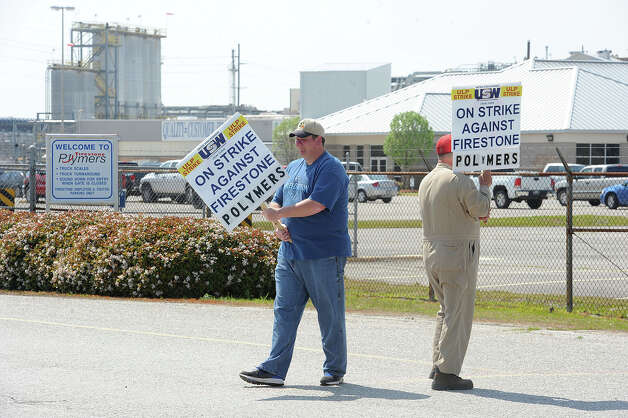 Members of Local No. 13-836 of the United Steelworkers union began striking Monday at Firestone Polymers in Orange after negotiations failed to resolve issues that included a wage increase and health insurance deductibles. The union has 108 members who will work in four-member shifts with two members picketing at a time. About 20 nonunion hourly workers are affected by the strike, but won't be picketing, a union official said. Gary Brinson, right, and Randall Hetzel picket the front gate of Firestone Polymers in the strike that began noon Monday.    Photo taken Monday, March 18, 2013 Guiseppe Barranco/The Enterprise Photo: Guiseppe Barranco, STAFF PHOTOGRAPHER / The Beaumont Enterprise