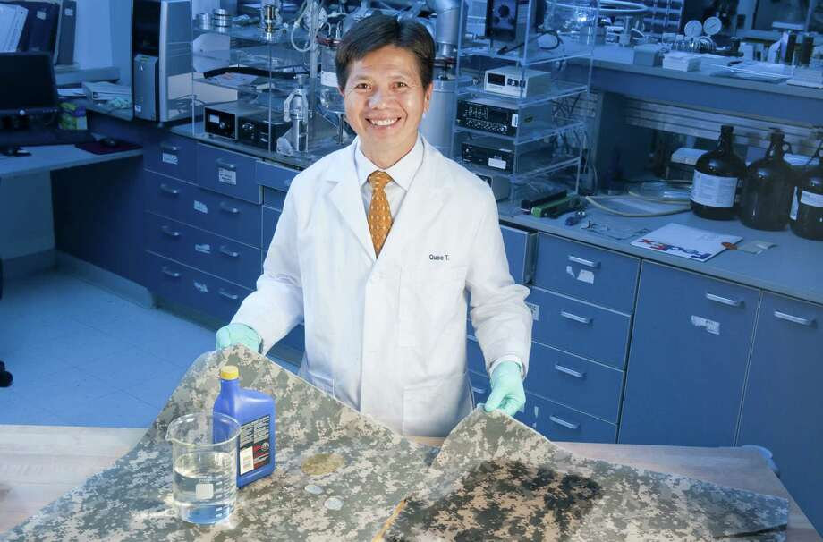 Quoc Truong, with Natick Soldier Research, Development and Engineering Center, shows the difference between self-cleaning clothing and regular Army Combat Uniforms when they are exposed to liquids. Photo: Army Research Center