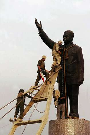 U.S marines climb up to topple a statue of Iraqi dictator Saddam Hussein on April 9, 2003 at al-Fardous square in Baghdad, Iraq..  The third year anniversary since the overthrow of Saddam Hussein will be marked on April 9, 2006 amidst continued unrest in Iraq, where over 30, 000 civilians have been reported to be killed since the start of the war. Photo: Wathiq Khuzaie, Getty Images