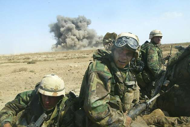 Marines react after a U.S. missile destroyed the building behind them March 23, 2003, in southern Iraq. Photo: Joe Raedle, Sfc
