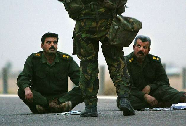 Iraqi Lt. Colonels sit on the ground after surrendering themselves and their troops March 21, 2003 in Safwan, Iraq.  Chaos reigned in southern Iraq March 21, as coalition troops continued their offensive to remove Iraqi president Saddam Hussein. Photo: Chris Hondros, Sfc