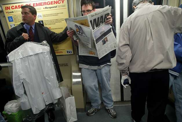 On an inbound BART train,  Mike Montero of San Francisco read the paper the morning after war broke out in Iraq. Photo: Mike Kepka, SFC
