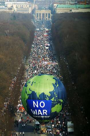 A Greenpeace balloon leads a group of anti-war protesters from the Brandenburg Gate to the Victory Column during an anti-war protest March 29, 2003 in Berlin, Germany. Over 50,000 people took to the streets in Berlin in a peaceful protest against the U.S.-led war in Iraq.  Photo: Kurt Vinion, Getty Images