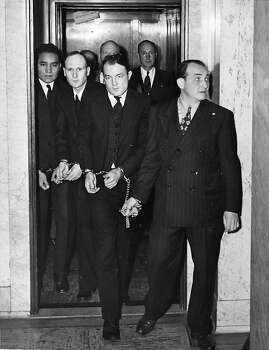 Shackled together (left to right): Clarence Carnes, 19, Sam Shockley and Miran Thompson are led from an elevator in the San Francisco Federal building on June 25, 1946 en route to court in custody of a U.S. Marshal for arraignment on a murder charge stemming from an abortive break at Alcatraz on May 2-4, 1946. Photo: Associated Press