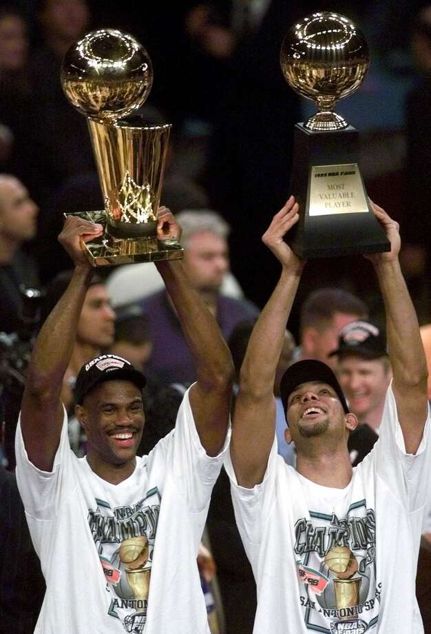 The Spurs' David Robinson (left) holds up the NBA Championship trophy as teammate Tim Duncan holds up the Most Valuable Player trophy after defeating the New York Knicks 78-77 in Game 5 of the 1999 NBA Finals on June 25, 1999, at New York's Madison Square Garden. Photo: MARK LENNIHAN, AP / AP