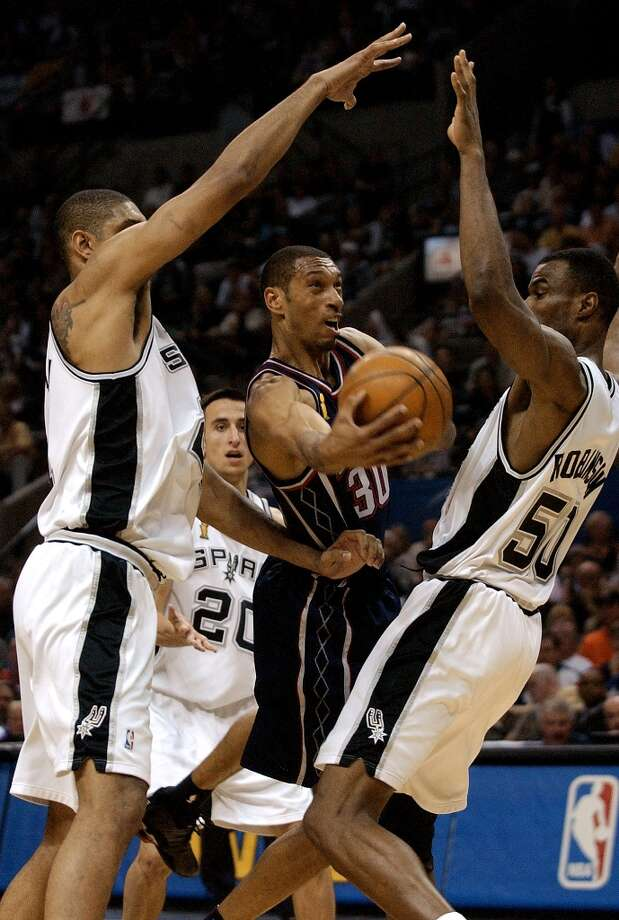 The Nets' Kerry Kittles cuts through Spurs Tim Duncan and David Robinson, right as he drives to the hoop during third quarter action of Game 6 of the NBA Finals at the SBC Center in San Antonio on June 15, 2003. Photo: KIN MAN HUI, SAN ANTONIO EXPRESS-NEWS / SAN ANTONIO EXPRESS-NEWS