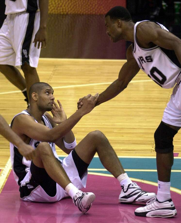 David Robinson helps Tim Duncan up from the court after Duncan was fouled during fourth period at the Alamodome on May 21, 2001. Photo: JERRY LARA, SAN ANTONIO EXPRESS-NEWS / SAN ANTONIO EXPRESS NEWS