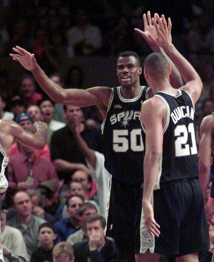 The Spurs' David Robinson (50) gives a high-five to teammate Tim Duncan (21) during the first half of Game 5 of the 1999 NBA Finals against the New York Knicks on June 25, 1999, at New York's Madison Square Garden. Photo: RON FREHM, AP / AP