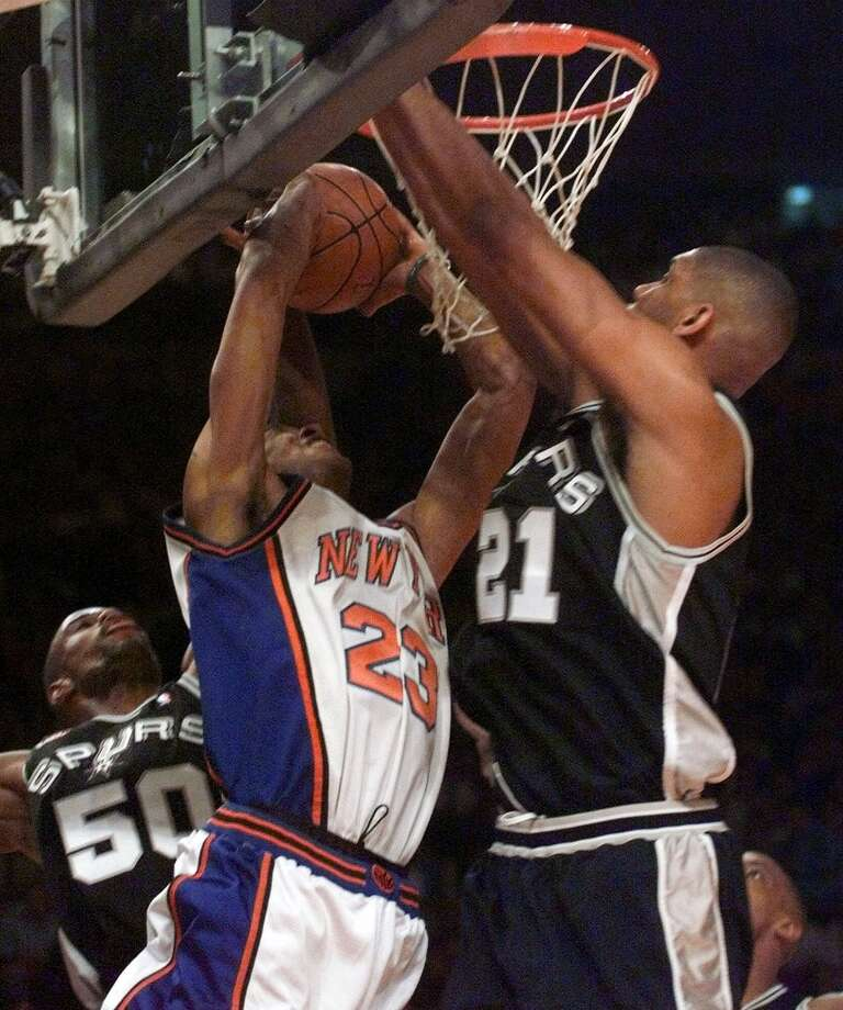 The Knicks' Marcus Camby (23) and Spurs' Tim Duncan (21) fight for a rebound during Game 3 of the NBA Finals on June 21, 1999, at New York's Madison Square Garden. At left is the Spurs' David Robinson. Photo: RON FREHM, AP / AP