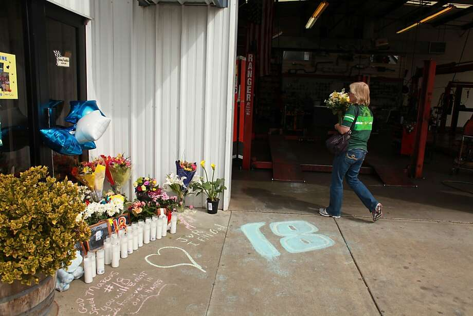 A visitor leaves flowers in memory of Marcus Johnson at the family's Johnny Franklin's Mufflers shop in Santa Rosa. Photo: Sam Wolson, SFC