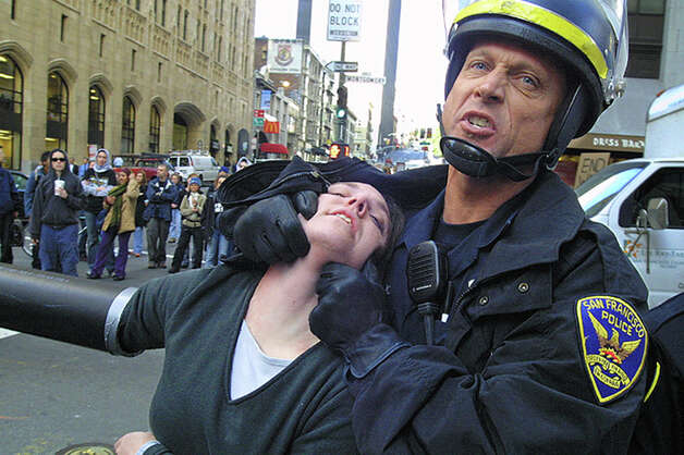 San Francisco police officer Kevin Dempsey subdues demonstrator Marianna Ditturo during anti-war protests in the Financial District of San Francisco on Thursday, March 20, 2003. Montgomery and Pine was one of several intersections clogged by protesters the morning after the United States-led coalition began bombing Iraq. Over 1400 protesters were arrested. Photo: Douglas Zimmerman / SF Gate