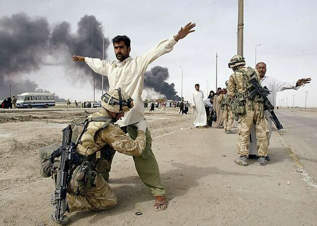 British soldiers check Iraqis leaving the southern Iraqi town of Basra, 30 March 2003. Several Iraqi soldiers were arrested trying to escape intense fighting by putting on civilian clothes over their uniforms and attempting to slip through British checkpoints, according to Irish Guard Captain Alex Cosby. Photo: Odd Andersen, AFP/Getty Images