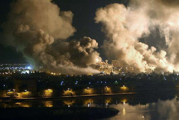 Smoke covers the presidential palace compound in Baghdad 21 March 2003 during a massive US-led air raid on the Iraqi capital. Smoke billowed from a number of targeted sites, including one of President Saddam Hussein's palaces. Photo: Ramzi Haidar, AFP/Getty Images