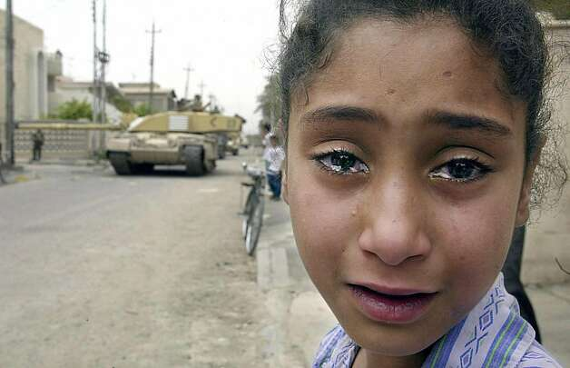 A young Iraqi girl cries as a British Challenger tank moves in on the Baath party office in Basra 08 April 2003. British and coalition forces took control over Iraq's second city after two weeks of heavy fighting leading to widespread looting as Iraqi forces retreated over the Shatt Al-Arab river. On 20 March 2006 Iraq marks the third anniversary of the launch of the US-led invasion that toppled Saddam Hussein, a war that has plunged the country into a deadly insurgency despite a sweeping political transformation. Photo: Odd Andersen, AFP/Getty Images