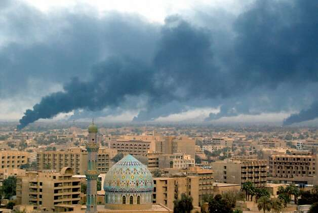 Smoke billowing from burning oil trenches covers Baghdad 02 April 2003. On 20 March 2006 Iraq marks the third anniversary of the launch of the US-led invasion that toppled Saddam Hussein, a war that has plunged the country into a deadly insurgency despite a sweeping political transformation. Photo: Patrick Baz, AFP/Getty Images