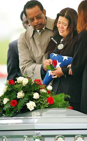 Hui Ok Davis (center), the widow of U.S. Army Sergeant First Class Wilbert Davis, holds an American flag and is comforted by friends as she mourns over her husband's casket at Arlington National Cemetery April 18, 2003 in Arlington, Virginia. Davis was killed in a vehicle accident along with journalist Michael Kelly April 3, 2003 in Iraq. Photo: Mike Theiler, Getty Images