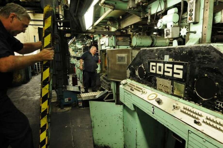 Times Union pressmen George Allen, left, and Tom Wagoner, attend to the Times Union's Goss Headliner MKII press during a production run Monday evening in Colonie, N.Y. Dec. 12, 2011. (Will Waldron / Times Union)