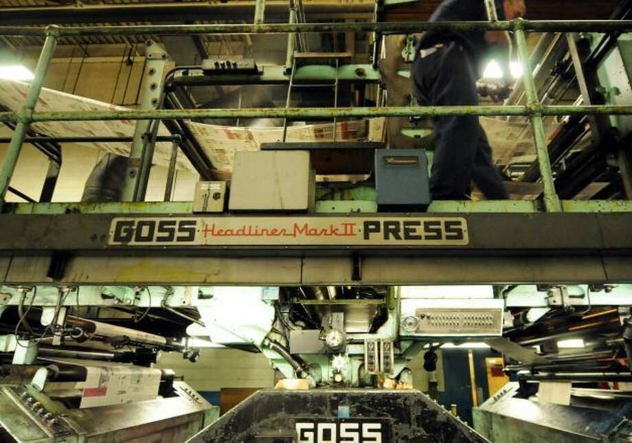 George Allen, Times Union pressman, right, attends to the Times Union's Goss Headliner MKII press during a production run Monday evening in Colonie, N.Y. Dec. 12, 2011. (Will Waldron / Times Union)