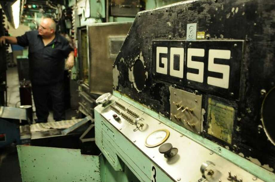Times Union pressman Tom Wagoner attends to the paper's Goss Headliner MKII press during a production run Monday evening in Colonie, N.Y. Dec. 12, 2011. (Will Waldron / Times Union)