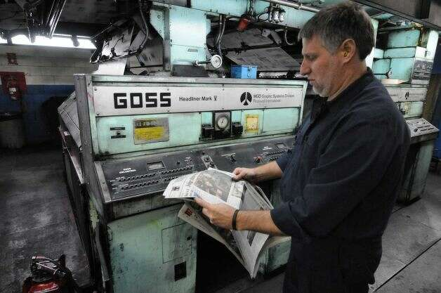 Times Union pressman Robert Care, right, makes color adjustments to the press early Sunday morning, Feb. 17, 2013, at the Times Union in Colonie, N.Y. Press operators constantly examine print and make adjustments to the press during the entire run. The Times Union?s Goss Headliner press was installed in 1970. (Will Waldron/Times Union)