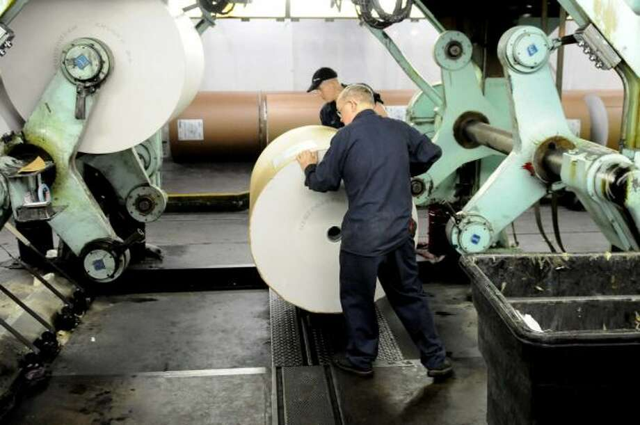 Erick Walter, left, Bill Parker, right, load a roll of newsprint on the Times Union?s press early Sunday morning, Feb. 17, 2013, at the Times Union in Colonie, N.Y. (Will Waldron/Times Union)