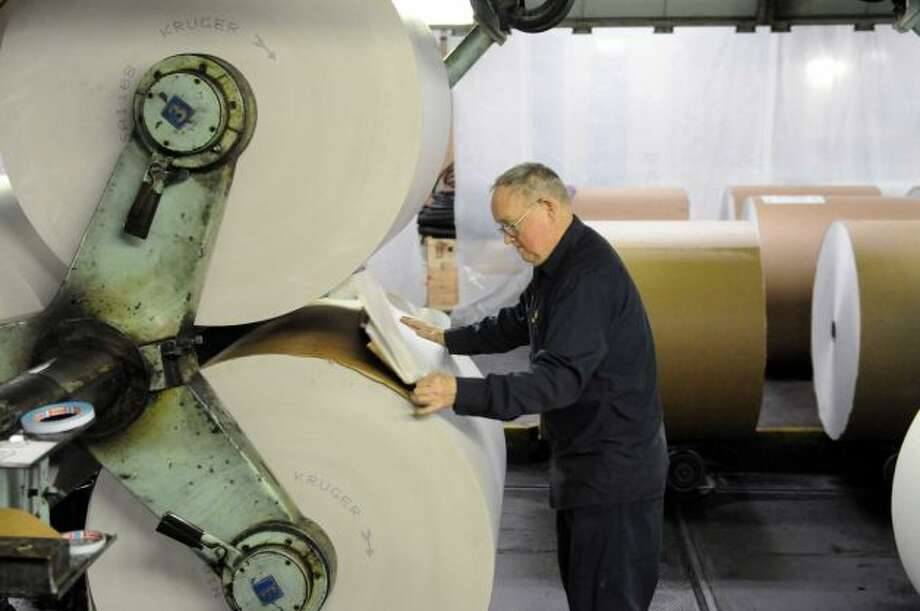 Bill Parker preps a roll of newsprint for splicing early Sunday morning, Feb. 17, 2013, at the Times Union in Colonie, N.Y. (Will Waldron/Times Union)