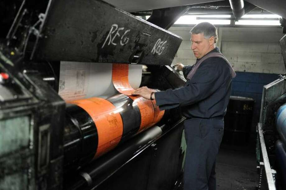 Pressman Robert Bottari puts on the last plates for the last run of the old Goss press at the Times Union on Sunday, March 17, 2013 in Colonie, N.Y. (Lori Van Buren / Times Union)