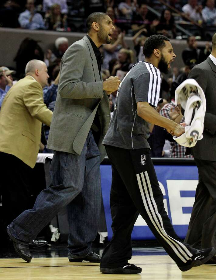 Spurs' Tim Duncan (center) and Patty Mills cheer on the guys on the floor against the New Orleans Hornets on Jan. 23, 2013. Spurs defeated the Hornets, 106-102. Photo: Kin Man Hui, San Antonio Express-News / © 2012 San Antonio Express-News