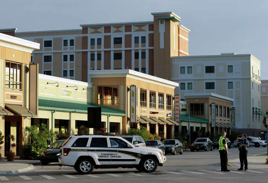 University of Central Florida police block off a street near the Tower 1 dorm, tall building center, after explosive devices were found by authorities investigating the apparent suicide of a college student in the dorm, Monday, March 18, 2013, in Orlando, Fla. Hundreds of students were evacuated, though the school said there was no immediate threat. (AP Photo/John Raoux) Photo: John Raoux
