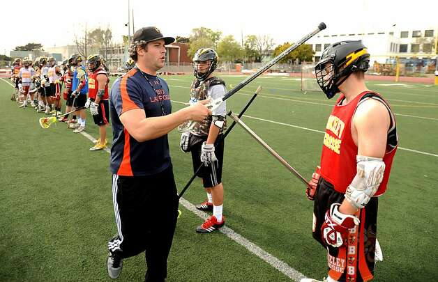 Chris May, head coach of the Berkeley High School men's lacrosse team, taps a player on his helmet while running practice drills on Monday, March 18, 2013, in Berkeley, Calif. On Monday, the American Academy of Neurology  published updated guidelines regarding athletes and concussions. Photo: Noah Berger, Special To The Chronicle