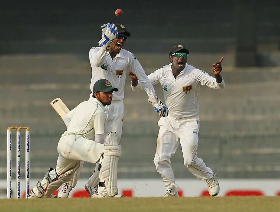 Sri Lankan wicket keeper Dinesh Chandimal, center, and captain Angelo Mathews, left, unsuccessfully appeal for the wicket of Bangladeshi batsman Monimul Haque during the third day of the second test cricket match in Colombo, Sri Lanka, Monday, March 18, 2013. (AP Photo/Eranga Jayawardena) Photo: Eranga Jayawardena, Associated Press