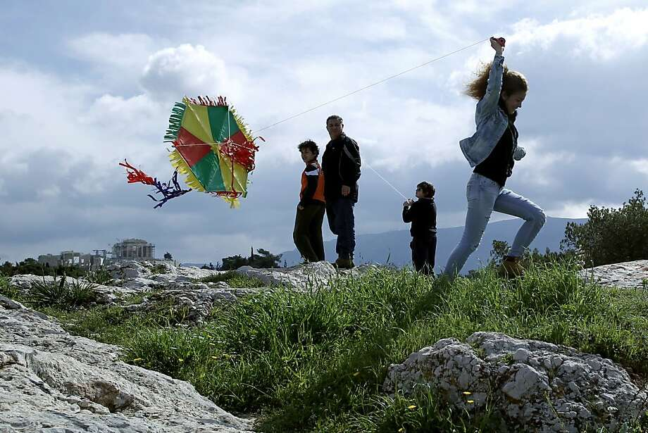 A young woman attempts to launch her kite on 'Clean Monday' at Filopappos hill with the ancient Parthenon temple seen in the background left, Athens, March 18, 2013. Many Greeks commemorate 'CleanMonday', the first day of Lent, by flying kites and eating foods associated with fasting. (AP Photo/Petros Giannakouris) Photo: Petros Giannakouris, Associated Press