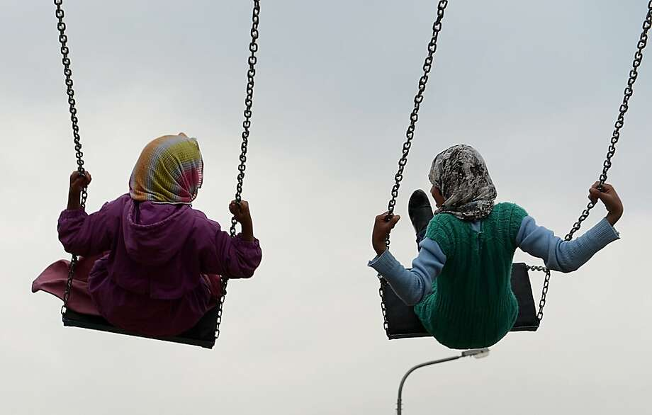 Young Afghan girls play on swings near The Kart-e-Sakhi shrine in Kabul on March 18, 2012. Despite massive injection of foreign aid since the fall of the Taliban in 2001, Afghanistan remains desperately poor with some of the lowest living standards in the world.  SHAH MARAI/AFP/Getty Images Photo: Shah Marai, AFP/Getty Images